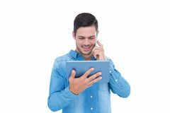 Handsome hipster on the phone holding tablet Royalty Free Stock Image