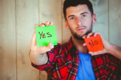 Handsome hipster showing yes and no cards. Against wooden background Stock Photography
