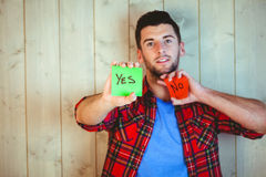 Handsome hipster showing yes and no cards. Against wooden background Royalty Free Stock Photos