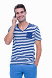 Handsome hipster smiling at camera and having a phone call Royalty Free Stock Photo