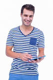 Handsome hipster smiling at camera and holding tablet Royalty Free Stock Image