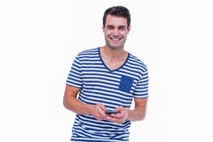 Handsome hipster smiling at camera and using smartphone Royalty Free Stock Image