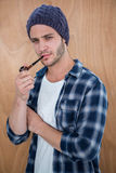 Handsome hipster smocking a pipe Royalty Free Stock Image