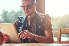 Handsome hipster with a stylish haircut and beard sits at a table in a roadside cafe, looks something in the tablet.  Royalty Free Stock Photography