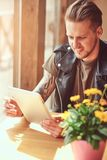 Handsome hipster with a stylish haircut and beard sits at a table in a roadside cafe, looks something in the tablet.  Stock Images