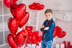 Handsome hipster teen posing with red heart baloon in studio. Young man in yellow shirt going to the date over studio. Background Stock Photography