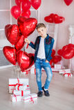 Handsome hipster teen posing with red heart baloon in studio. Young man in yellow shirt going to the date over studio. Background Royalty Free Stock Photos
