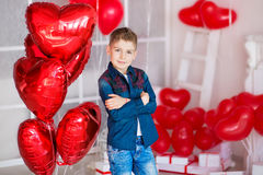 Handsome hipster teen posing with red heart baloon in studio. Young man in yellow shirt going to the date over studio. Background Stock Photos