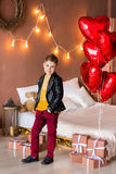 Handsome hipster teen posing with red heart baloon in studio. Young man in yellow shirt going to the date over studio. Background Royalty Free Stock Photo
