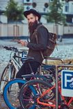A handsome hipster traveler with a stylish beard and tattoo on h. Handsome hipster traveler with a stylish beard and tattoo on his arms dressed in casual clothes stock photos
