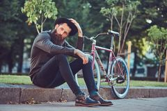 A handsome hipster traveler with a stylish beard and tattoo on his arms dressed in casual clothes and hat with a bag. Handsome hipster traveler with a stylish royalty free stock image