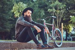 A handsome hipster traveler with a stylish beard and tattoo on his arms dressed in casual clothes and hat with a bag stock photo