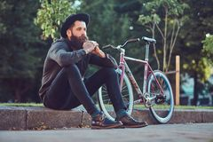A handsome hipster traveler with a stylish beard and tattoo on his arms dressed in casual clothes and hat with a bag stock photography