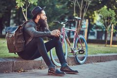 A handsome hipster traveler with a stylish beard and tattoo on his arms dressed in casual clothes and hat with a bag. Handsome hipster traveler with a stylish royalty free stock photo
