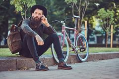 A handsome hipster traveler with a stylish beard and tattoo on his arms dressed in casual clothes and hat with a bag royalty free stock image