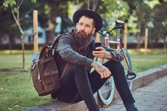 A handsome hipster traveler with a stylish beard and tattoo on his arms dressed in casual clothes and hat with a bag royalty free stock photography