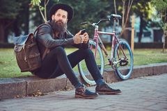 A handsome hipster traveler with a stylish beard and tattoo on his arms dressed in casual clothes and hat with a bag stock images