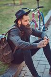 A handsome hipster traveler with a stylish beard and tattoo on his arms dressed in casual clothes and hat with a bag stock photos