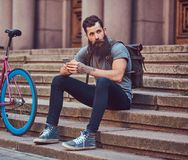 A handsome hipster traveler with a stylish beard and tattoo on his arms dressed in casual clothes, sitting on the steps royalty free stock image