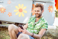 Handsome hipster using his smart phone. At a music festival Royalty Free Stock Images