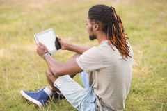 Handsome hipster using his tablet pc Royalty Free Stock Image