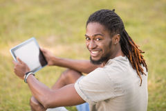 Handsome hipster using his tablet pc Royalty Free Stock Photography