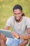 Handsome hipster using his tablet pc Royalty Free Stock Photos