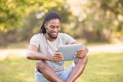 Handsome hipster using his tablet pc Royalty Free Stock Images