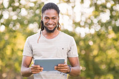 Handsome hipster using his tablet pc Stock Images