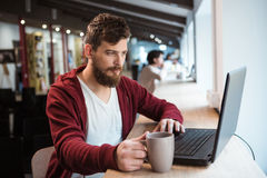 Handsome hipster using laptop and drinking coffee Stock Photos