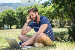 Handsome hipster using laptop in park Stock Image