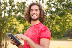 Handsome hipster using tablet pc in the park Stock Photo