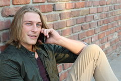 Handsome hipster young man with long blond hair sitting outdoors and talking on mobile phone royalty free stock image