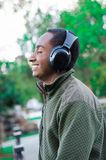 Handsome hispanic black man wearing green sweater in outdoors park area, headphones on covering ears and smiling. Enjoying some music, profile angle royalty free stock image