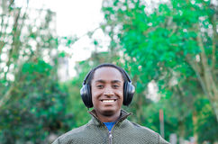 Handsome hispanic black man wearing green sweater in outdoors park area, headphones on covering ears and smiling Stock Photo