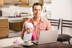 Handsome Hispanic dad working at home Royalty Free Stock Images