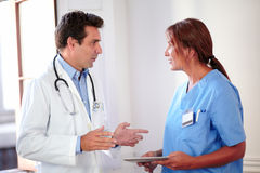 Handsome hispanic doctor talking with lady nurse Stock Photo