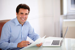 Handsome hispanic employee looking at you. Portrait of a handsome hispanic employee looking at you while holding documents and sitting on office desk Royalty Free Stock Photo