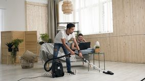Handsome hispanic gay dancing and cleanup with helping of the vacuum cleaner while his partner lover talking on the. Phone and using laptop in living room 4k stock footage