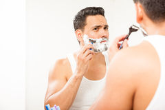 Handsome Hispanic man shaving his beard. Portrait of an attractive young Hispanic man using a razor to shave his beard in front of a bathroom mirror royalty free stock photo