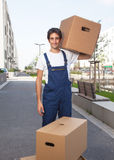 Handsome hispanic worker with boxes stock photo