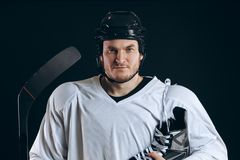 Handsome hockey player. Smiling at camera isolated on black background. stock photos