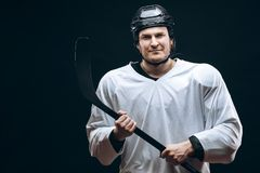 Handsome hockey player. Smiling at camera isolated on black background. stock image