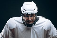 Handsome hockey player. Smiling at camera isolated on black background. royalty free stock photos