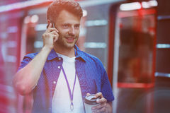 Handsome holding disposable cup while talking on mobile phone Royalty Free Stock Photo
