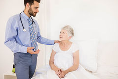 Handsome home nurse talking to elderly woman Stock Images