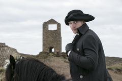 Handsome Horse Rider in Regency 18th Century Poldark Costume. Handsome Horse Rider in profile to camera on black horse with tricorn hat with the ruin of tin mine Royalty Free Stock Photo