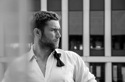 Handsome hunky man with unbuttoned shirt and loose bowtie stands on hotel balcony with sckyscraper backdrop. Handsome hunky male with loose bowtie and unbuttoned stock photos