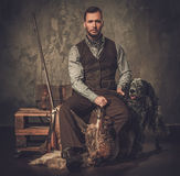 Handsome hunter with a english setter and shotgun in a traditional shooting clothing, sitting on a dark background. Stock Photo