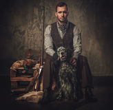 Handsome hunter with a english setter and shotgun in a traditional shooting clothing, sitting on a dark background. Handsome hunter with a english setter and Royalty Free Stock Photography